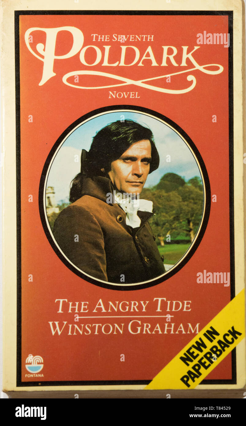 The Poldark novel The Angry Tide by Winston Graham with Ralph Bates as George Warleggan on the cover. - Stock Image