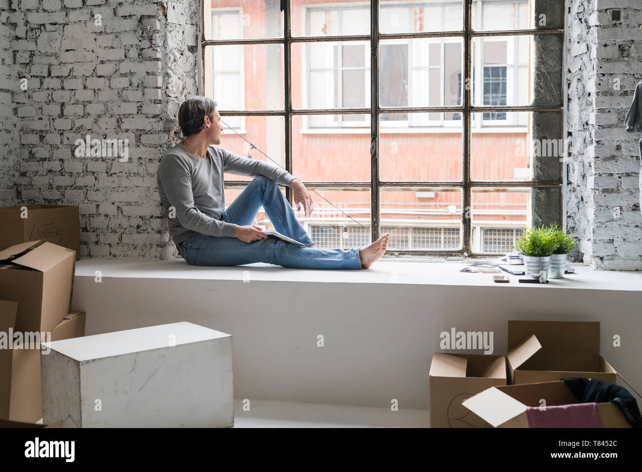 Man moving into industrial style apartment, sitting on window ledge looking through window - Stock Image
