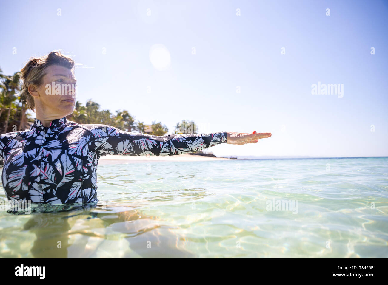 Woman stretching hand in sea, Pagudpud, Ilocos Norte, Philippines Stock Photo