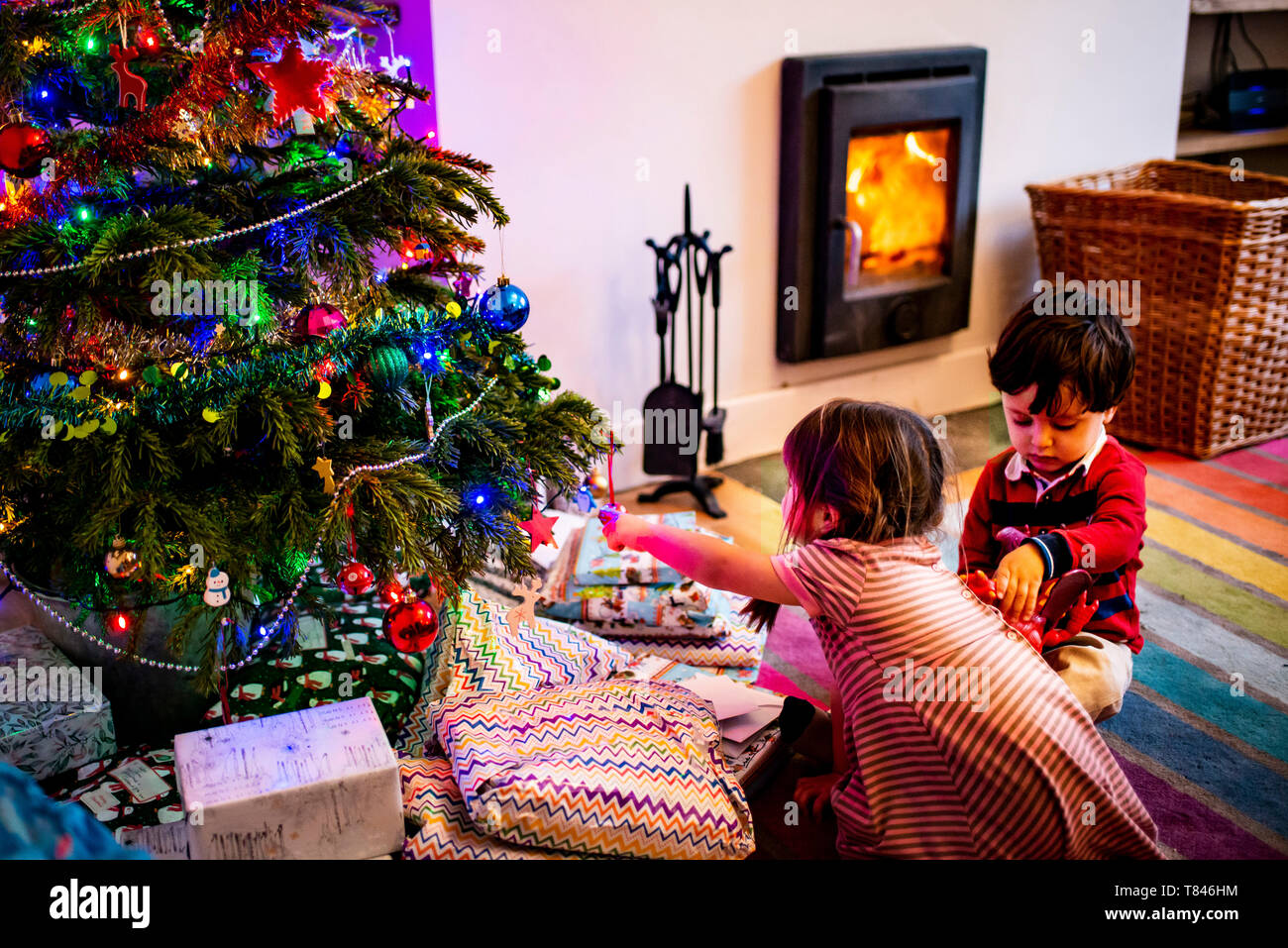 Girl and male toddler playing by living room christmas tree - Stock Image