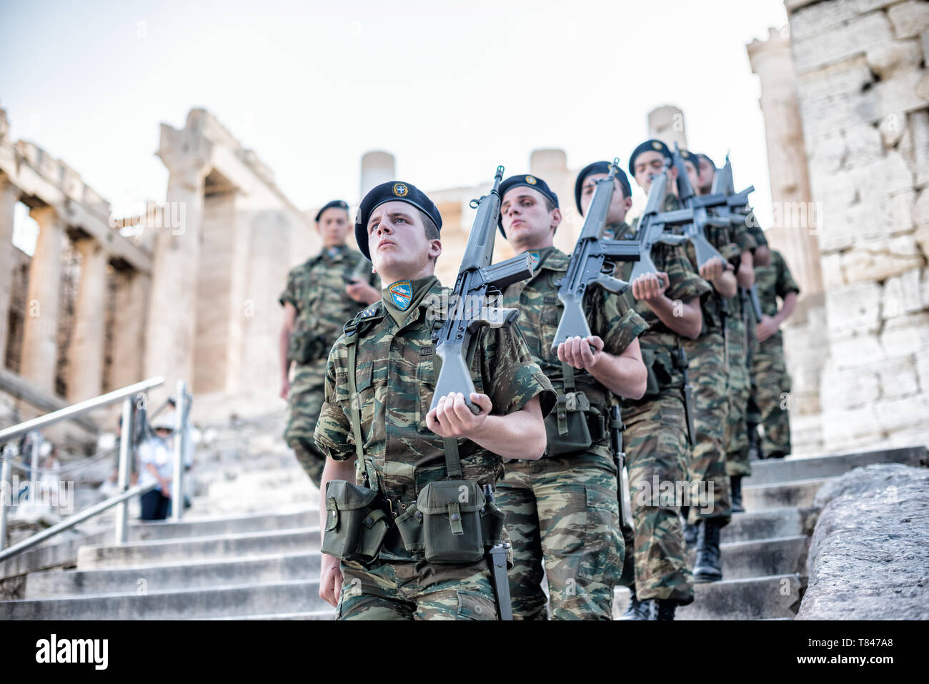 Greek soldiers march in formation while on patrol at the Acropolis of Athens. The Acropolis of Athens is an ancient citadel standing on a rocky outcro - Stock Image