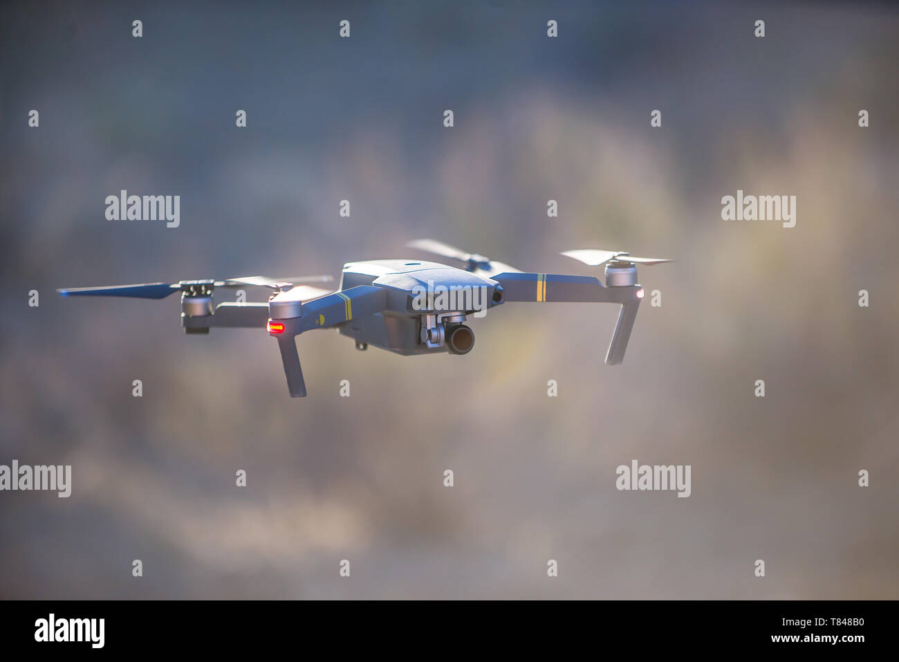 Drone (unmanned aerial vehicle) flying mid air, shallow focus - Stock Image