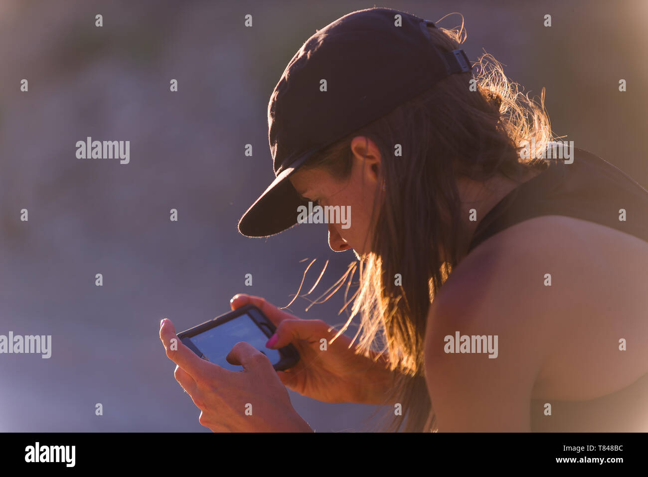 Woman operating drone (unmanned aerial vehicle) using smartphone - Stock Image