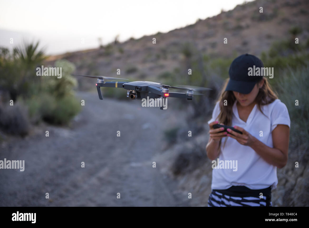 Woman operating drone (unmanned aerial vehicle) on rural dirt track - Stock Image