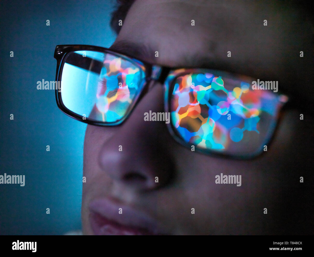 Biotechnology research, computer screen reflection in spectacles of new molecular formula in laboratory, close up of face - Stock Image