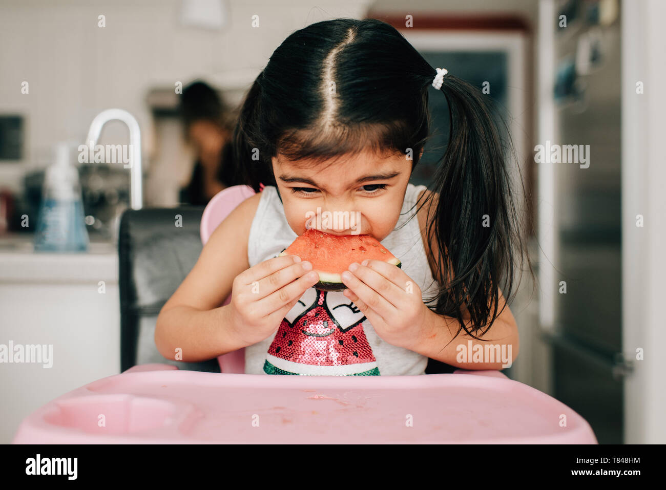 Girl in high chair eating water melon Stock Photo