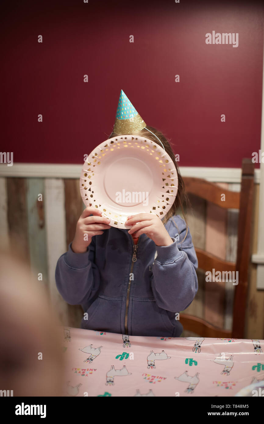 Birthday girl covering face with plate - Stock Image