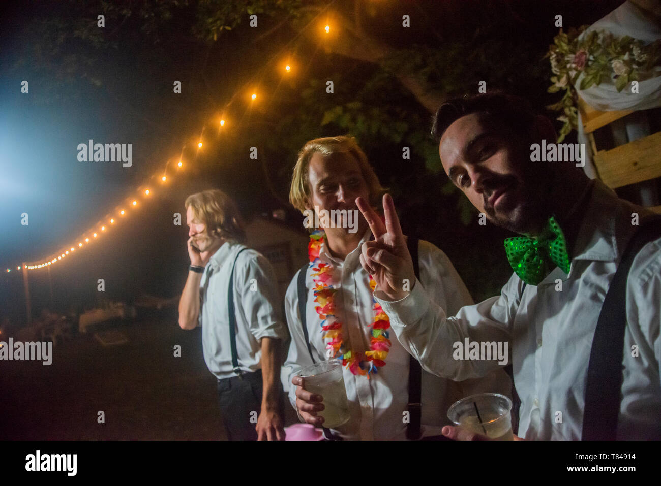 Young Men Making Peace Sign At Outdoor Wedding Reception At