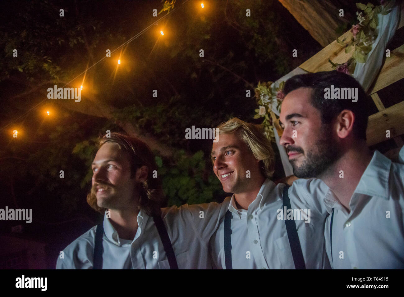 Three young men with arms around each other at outdoor wedding reception at night Stock Photo