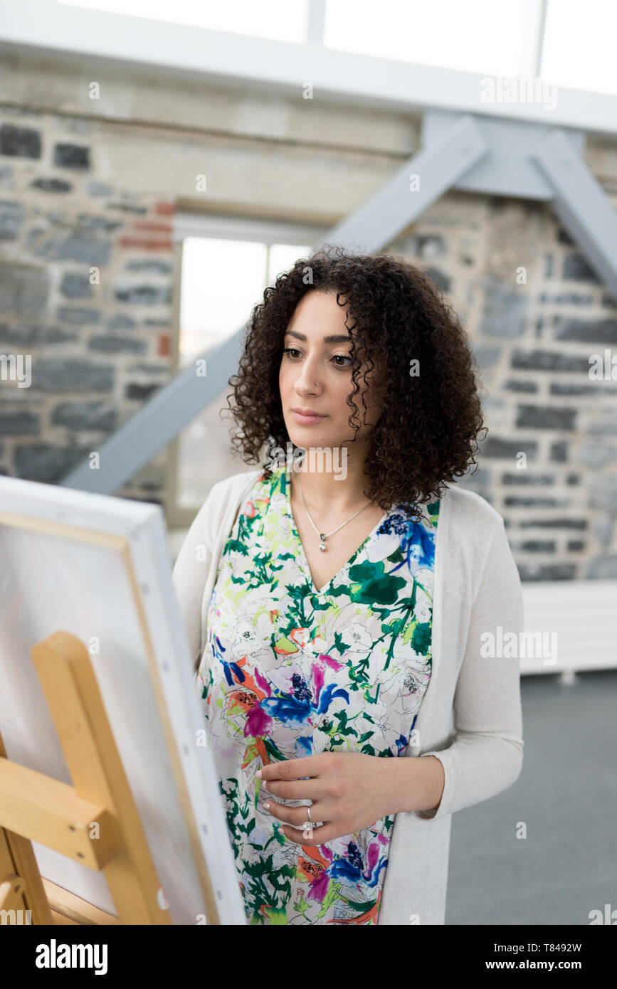 Young female painter painting canvas in studio - Stock Image