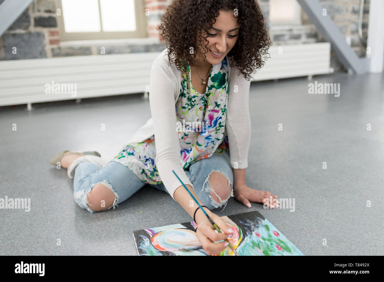 Young female painter painting canvas on studio floor - Stock Image