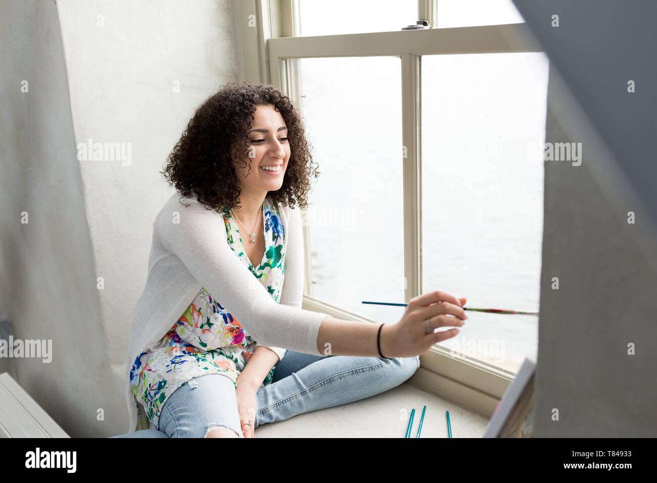Young female painter painting canvas on studio windowsill - Stock Image