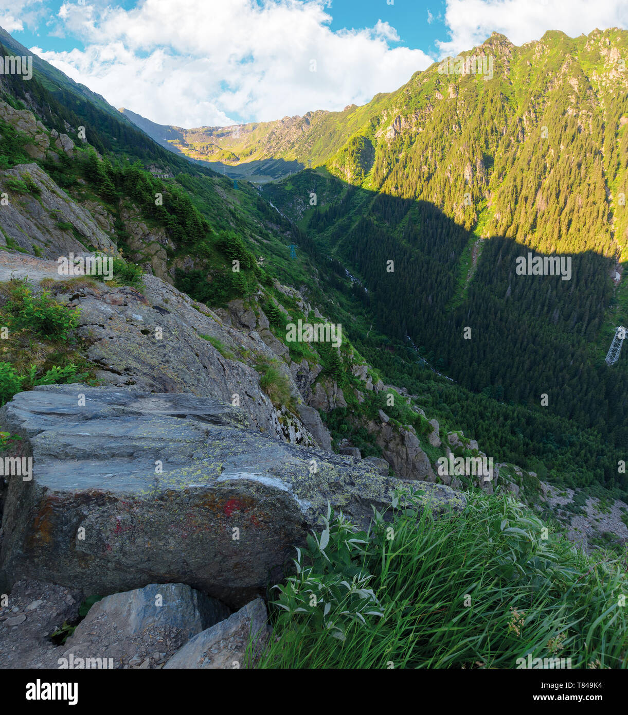 valley of the balea stream in fagaras mountains. view from the rocky cliff on a steep slope. forested hillside in the distance. popular travel destina - Stock Image