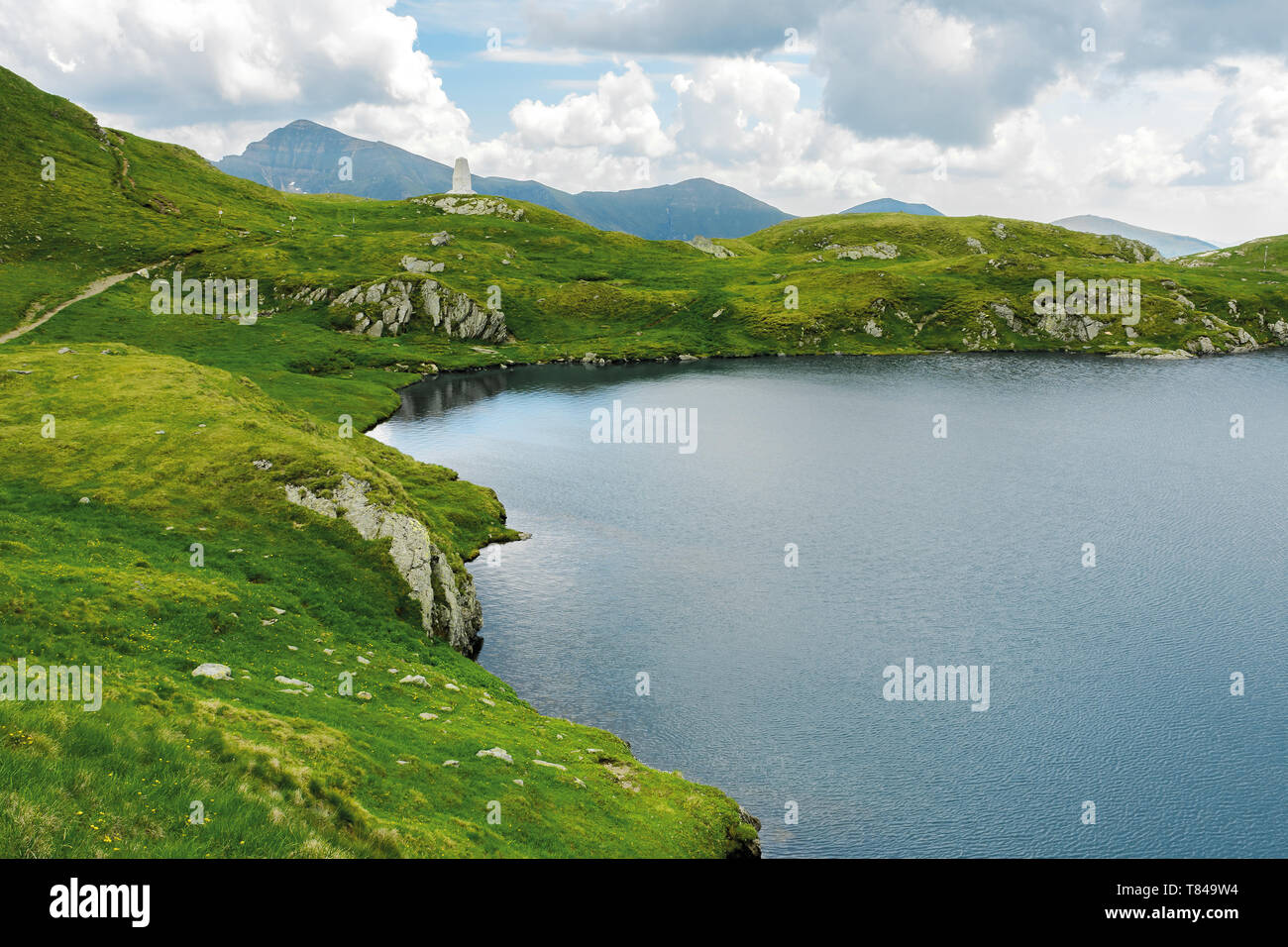 glacier mountain lake in summer. beautiful nature scenery in romania. wonderful background with water, grass, and rocks. location fagaras ridge - Stock Image