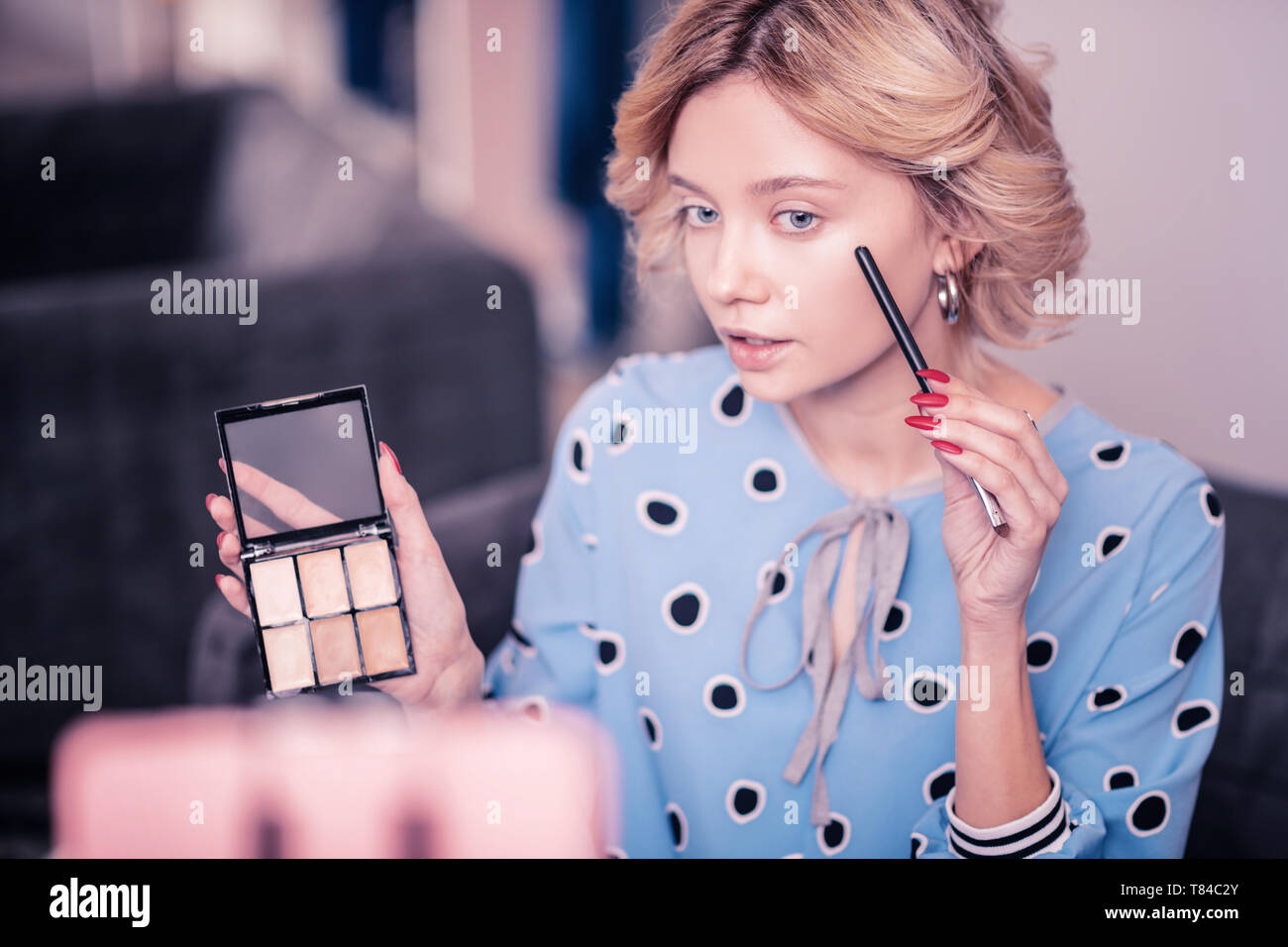 Blue-eyed beauty blogger telling some secrets about concealer - Stock Image