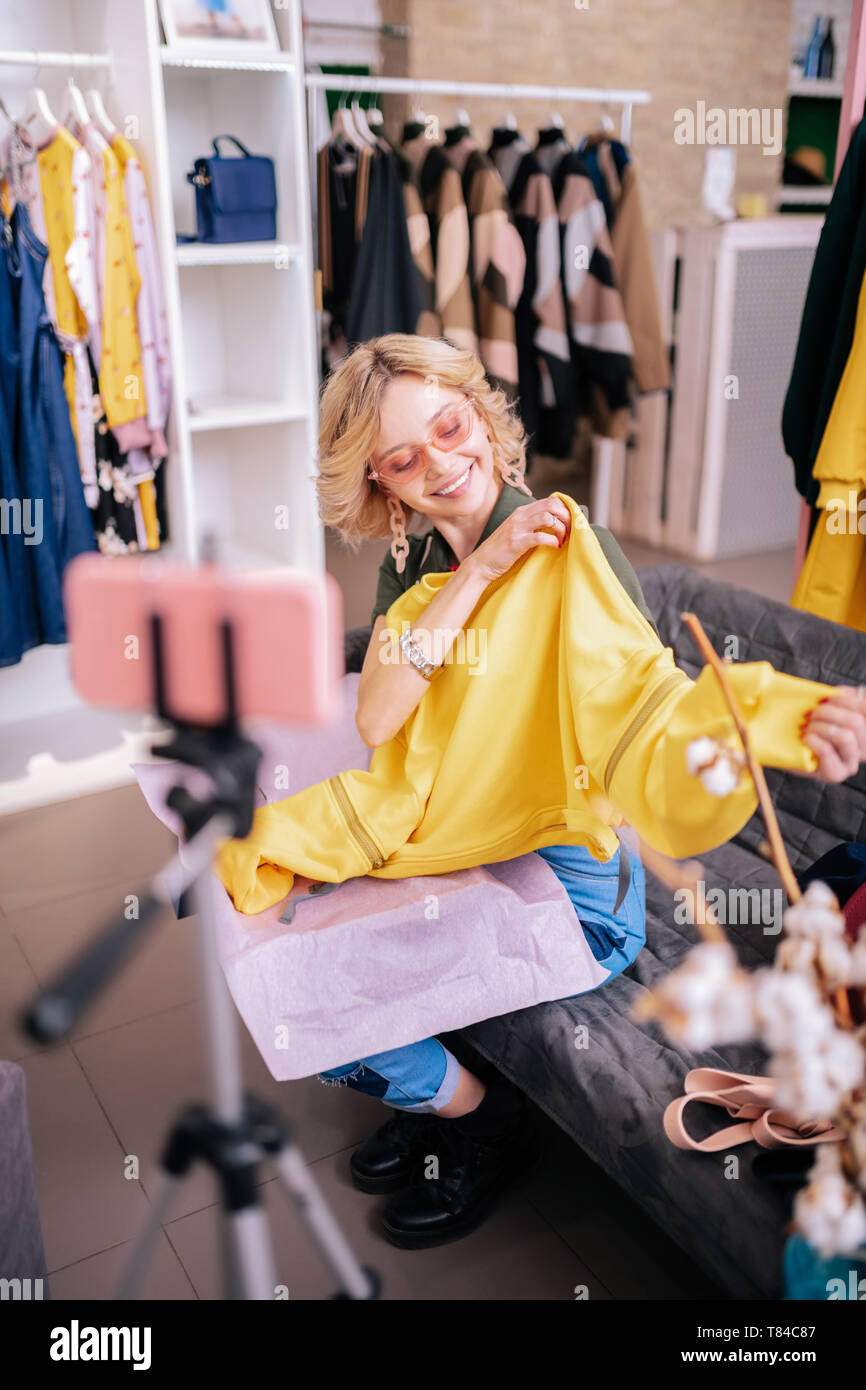 Blogger filming blog showing new yellow sweatshirt - Stock Image