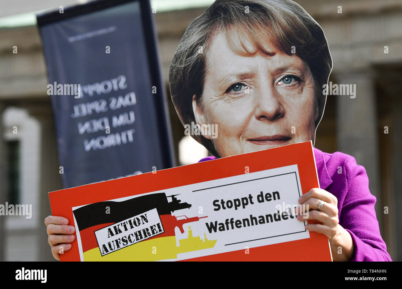 Berlin, Germany. 11th May, 2019. An activist with a mask by Federal Chancellor Angela Merkel stands in front of the Brandenburg Gate during an art action of the 'Aktion Aufschrei - Stoppt den Waffenhandel! The initiative protests against arms exports to warring parties in Yemen. Credit: Jens Kalaene/dpa-Zentralbild/dpa/Alamy Live News - Stock Image