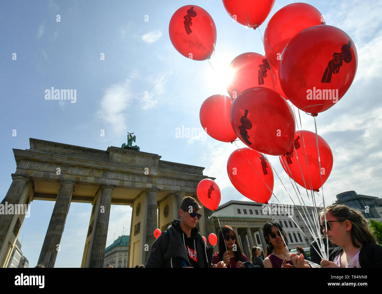 Berlin, Germany. 11th May, 2019. Balloons depicting a pistol with a knot in its barrel are distributed in front of the Brandenburg Gate during an art action of the 'Aktion Aufschrei - Stoppt den Waffenhandel! It is protesting against arms exports to war-participants in Yemen. Credit: Jens Kalaene/dpa-Zentralbild/dpa/Alamy Live News - Stock Image