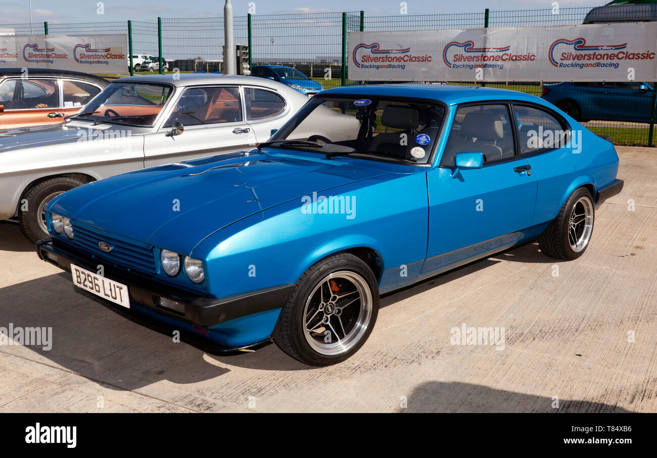 Three-quarters front view of a Blue, 1984  Ford Capri, in the Intentional Paddock, at the 2019 Silverstone Classic Media Day Stock Photo