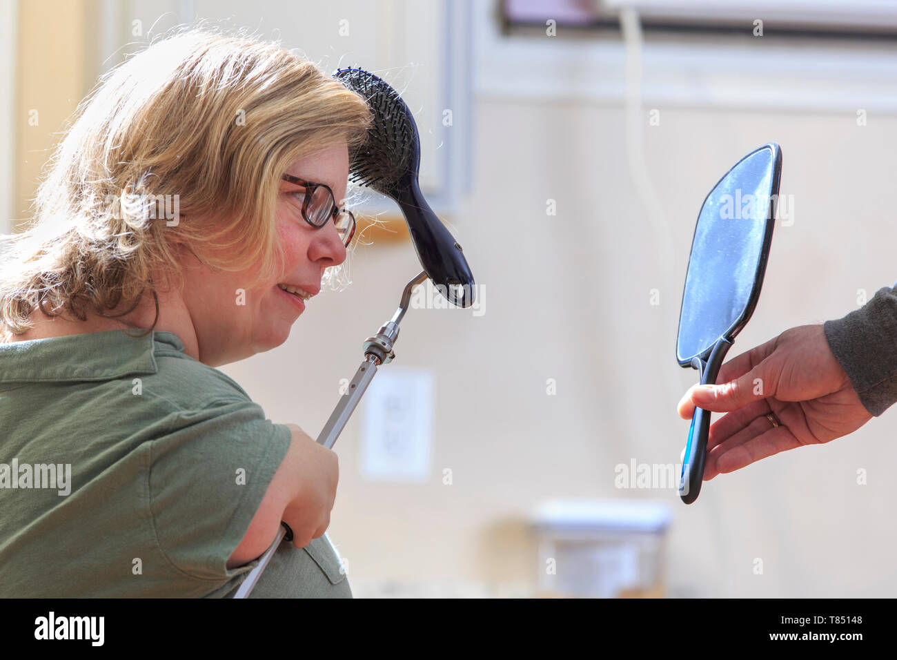 Woman with TAR Syndrome using an attachment to brush her hair - Stock Image