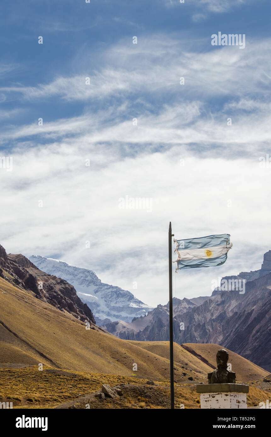 Argentina flag waving with historical bust and Aconcagua mountain behind. - Stock Image