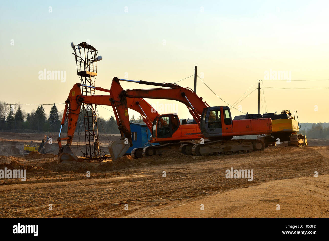 Group of the excavators in a quarry for the extraction of sand, gravel, rubble, quartz and other minerals - Image - Stock Image