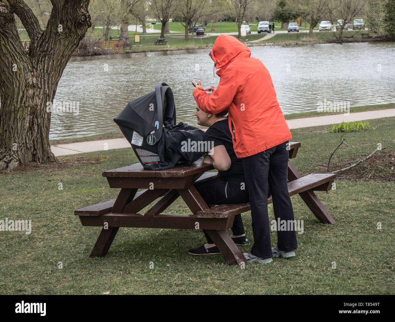 Two women and a toddler in the park in Stratford, Ontario. One of them takes a picture of the toddler. Cool grey day. - Stock Image