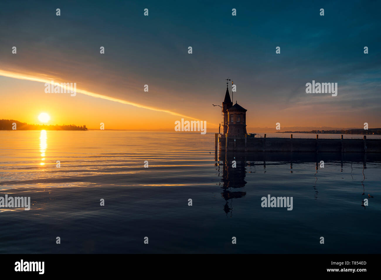 Early summer morning on lake Bodensee, Konstanz, Germany. Sunrise over water and lighthouse. Cloudscape and sun reflected on the water. - Stock Image
