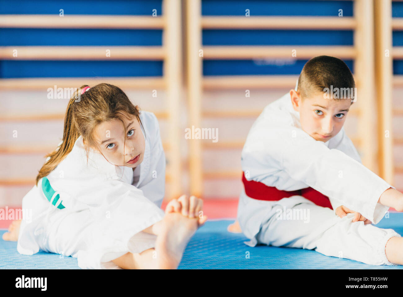 Children stretching in taekwondo class - Stock Image