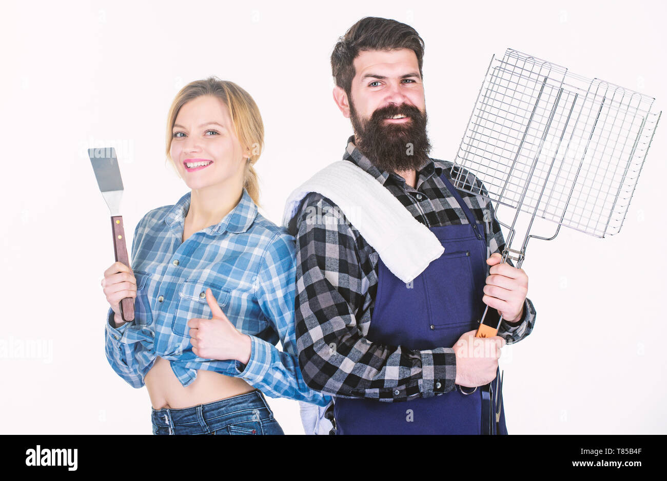 Tools for roasting meat. Couple in love hold kitchen utensils. Family weekend. Picnic barbecue. food cooking recipe. Man bearded hipster and girl. Preparation. Spending great time with friends. - Stock Image