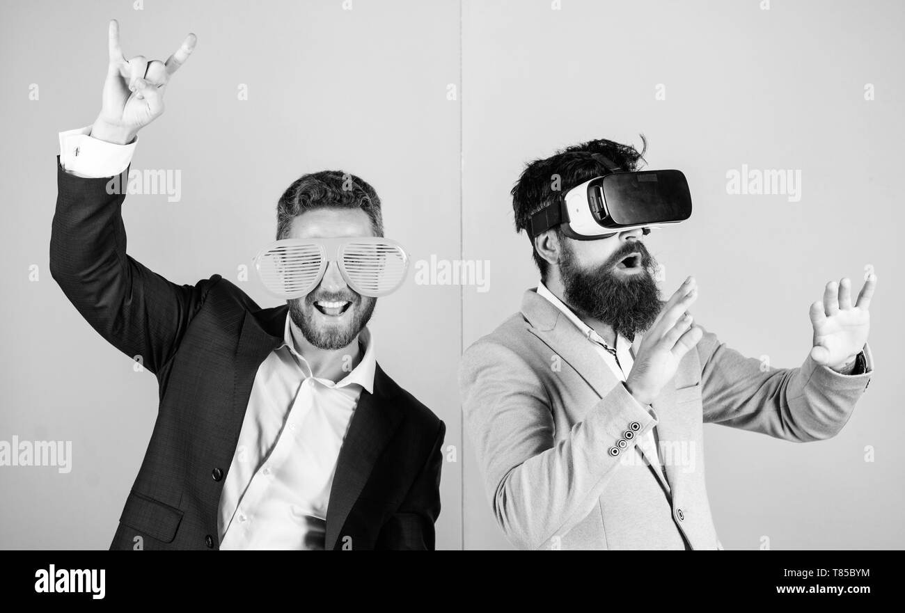 Real fun and virtual alternative. Man with beard in VR glasses and louvered plastic accessory. Guy interact in virtual reality. Hipster exploring virtual reality. Business implement modern technology. - Stock Image