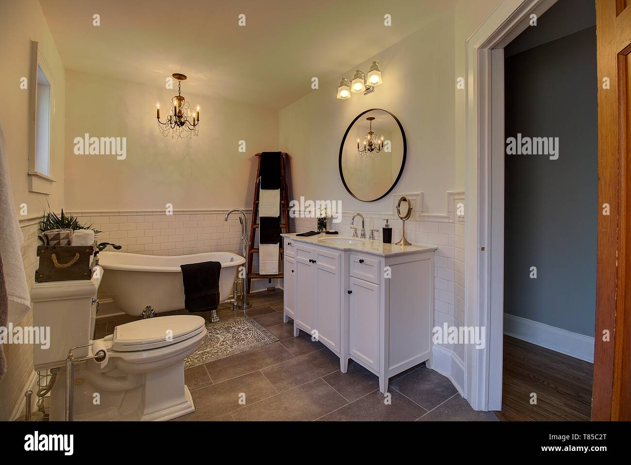 Home improvements. Claw foot tub modern cabinetry and subway tile floor to ceiling walls. - Stock Image