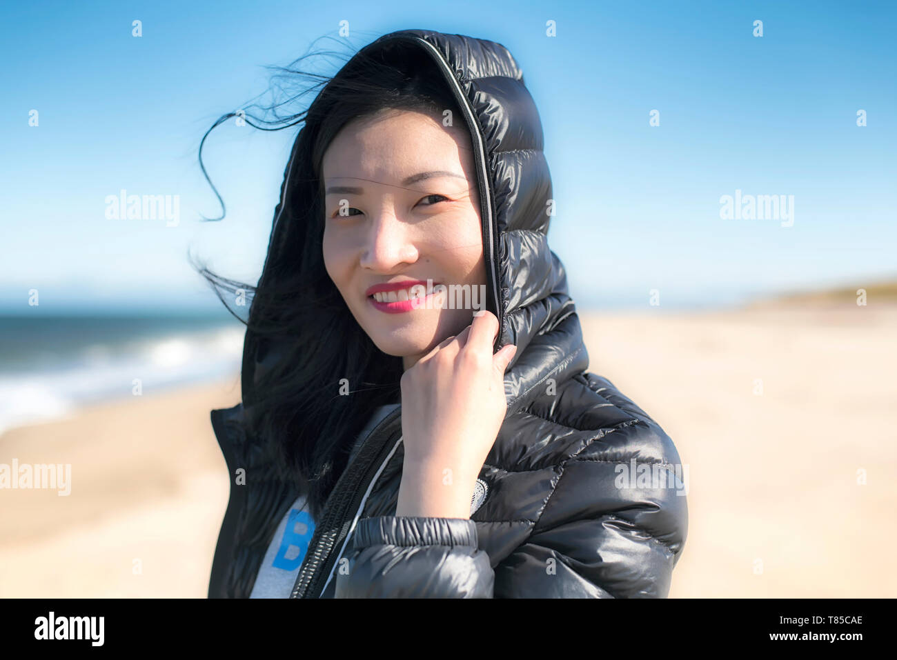 A Chinese woman smiling outside on a windy day on the Cape Cod National Seashore in Massachusetts. - Stock Image