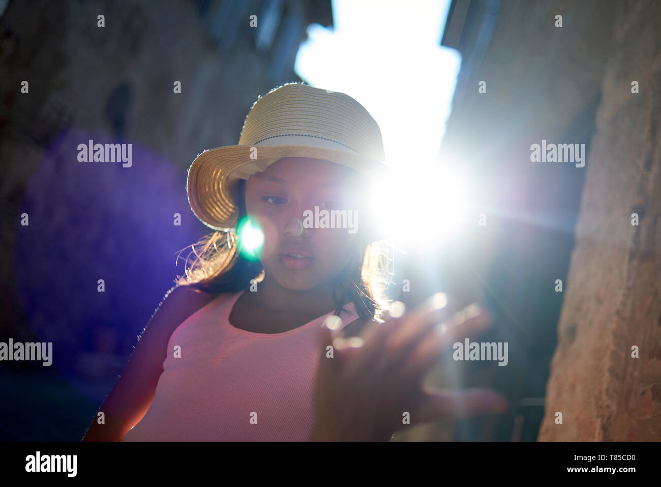 Mystical image of a cute preteen Asian girl wearing a straw hat in the streets of Siena in Toscany catching a beam of sunlight on her hand - Stock Image