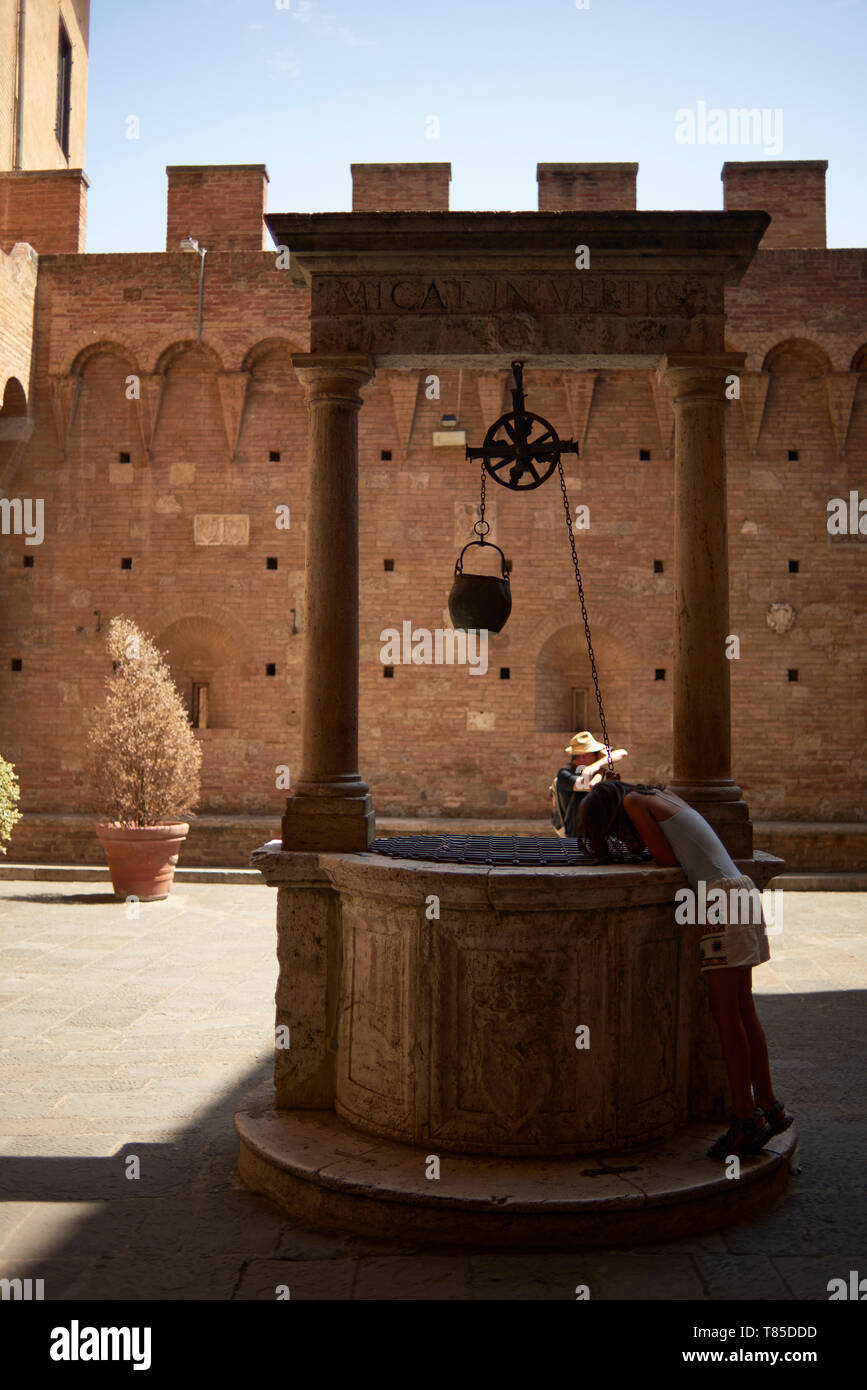 Kids looking into an old wishing well in the medieval city of Siena in Italy - Stock Image