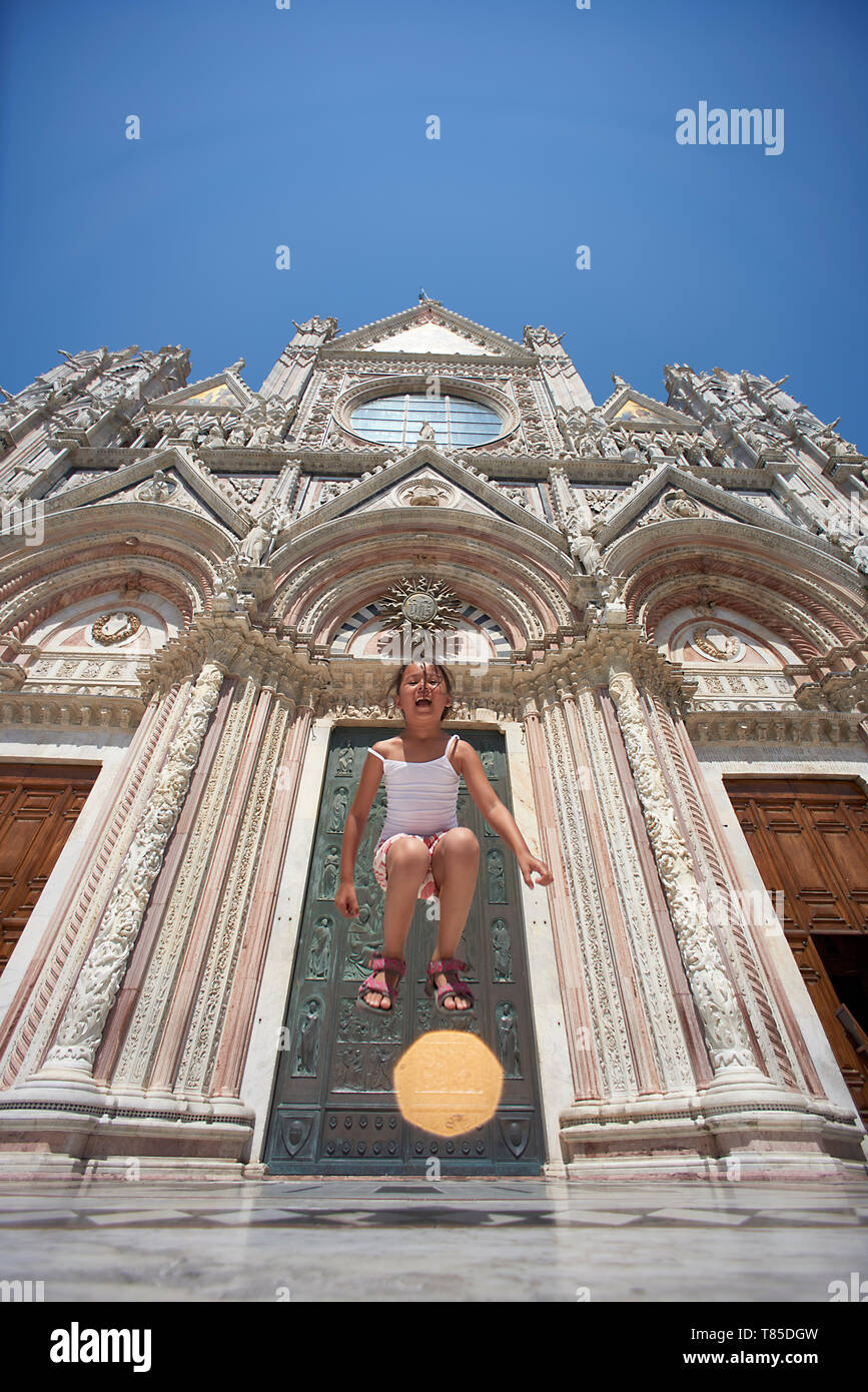 Amazing shot of a young Asian girl  full of positive energy happily jumping up high in the streets of Siena Toscany Italy in front of famous sights - Stock Image