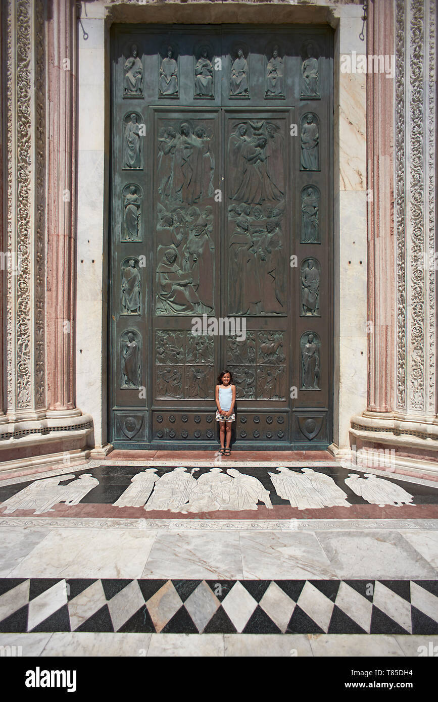 Beautiful shot of the big green door of the Cathedral in the city centre of Siena in Italy with a cute young Asian girl posing in front of it - Stock Image