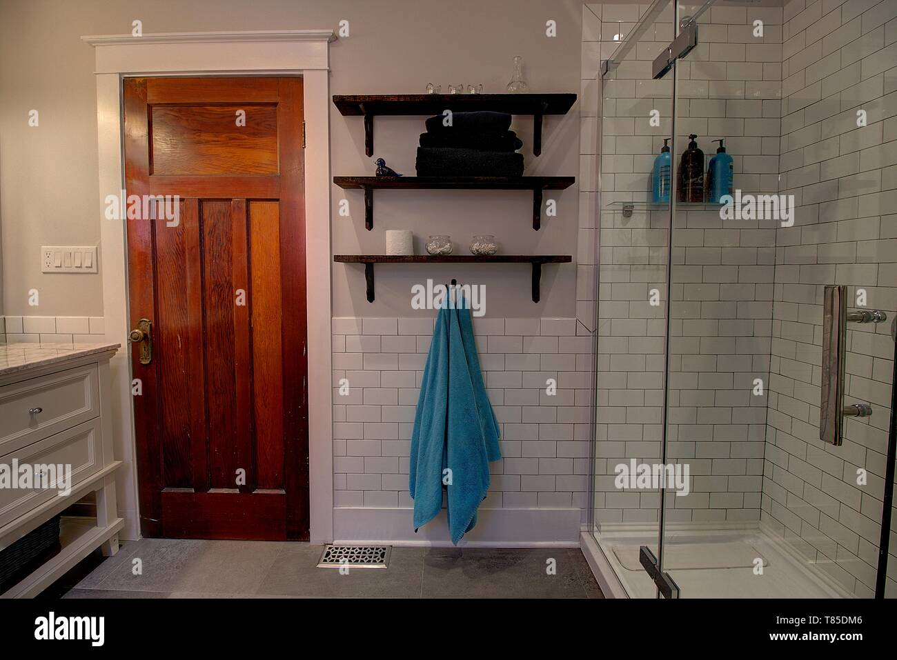 Modern bathroom renovation with subway tile and old wood door. Upadte home decor. - Stock Image