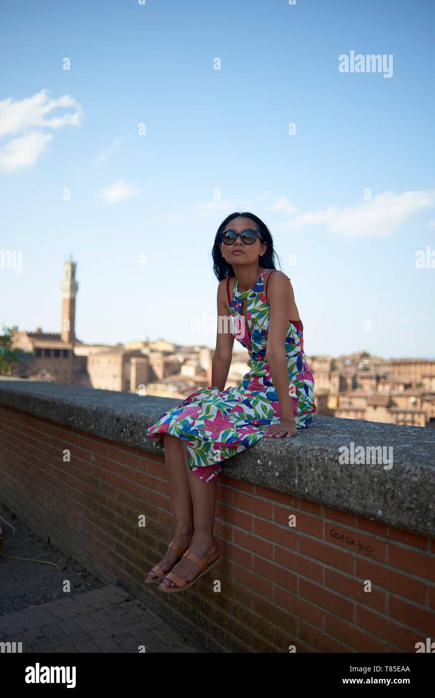 Beautiful Asian female tourist enjoying the sights and streets of Siena in Toscany Italy in bright summer sunshine - Stock Image