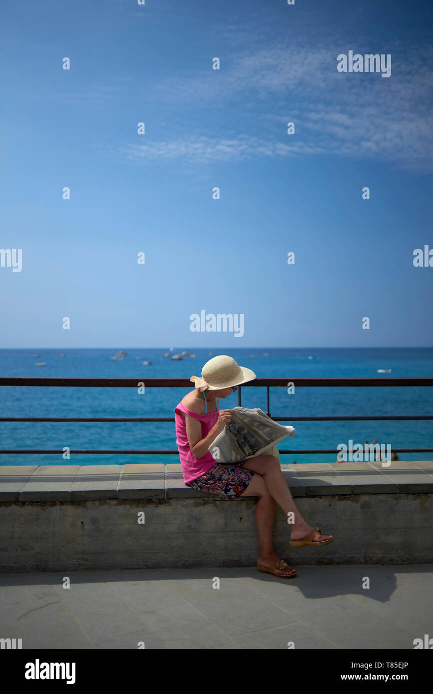 Asian woman wearing a big straw hat reading a newspaper whilst sitting and enjoying the seaside town in the Cinque Terra region of Italy in sunshine - Stock Image