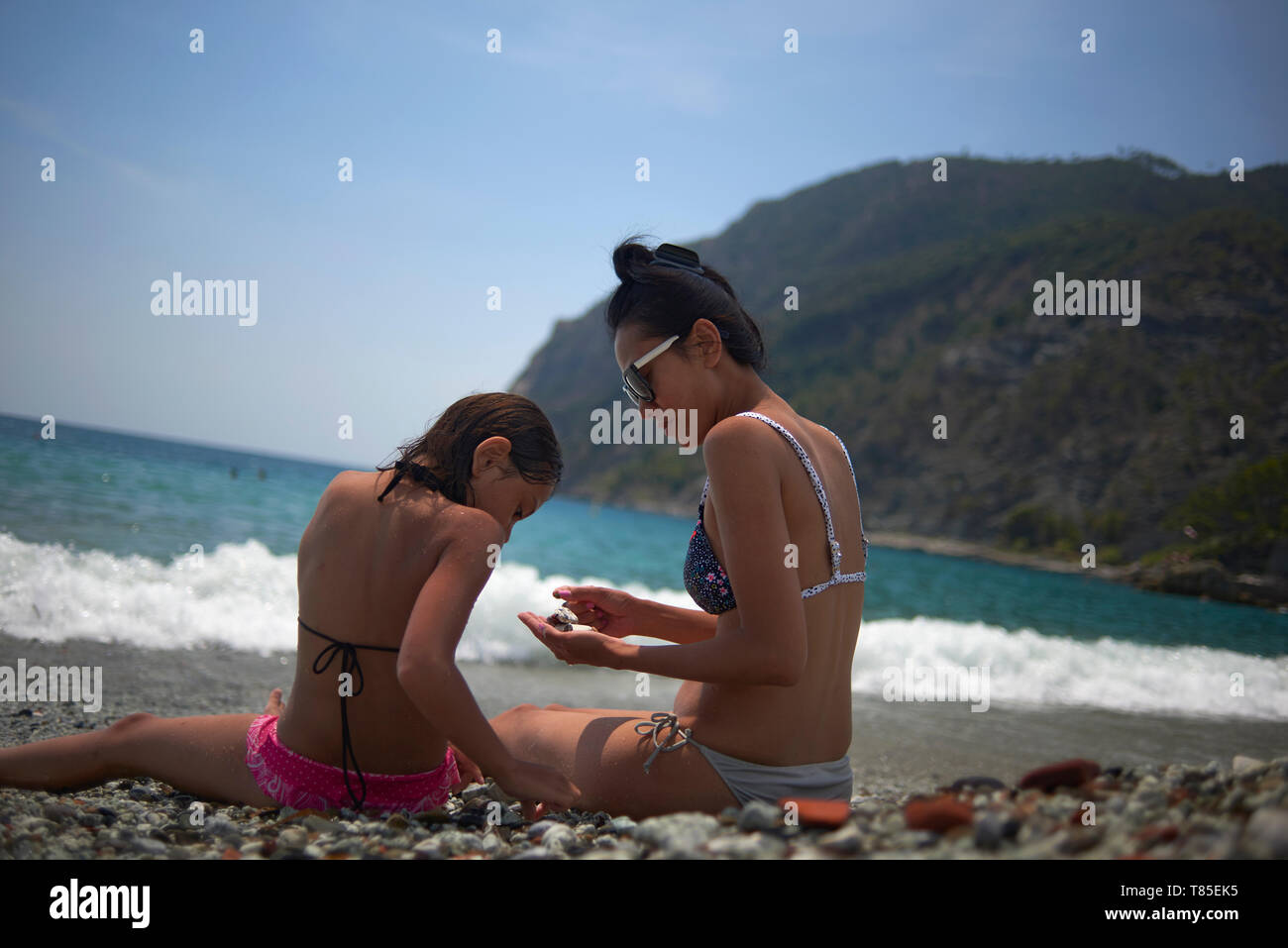 Asian mother and her two young daughters enjoying the beach along the Cinque Terra region in Italy in bright summer sunshine - Stock Image
