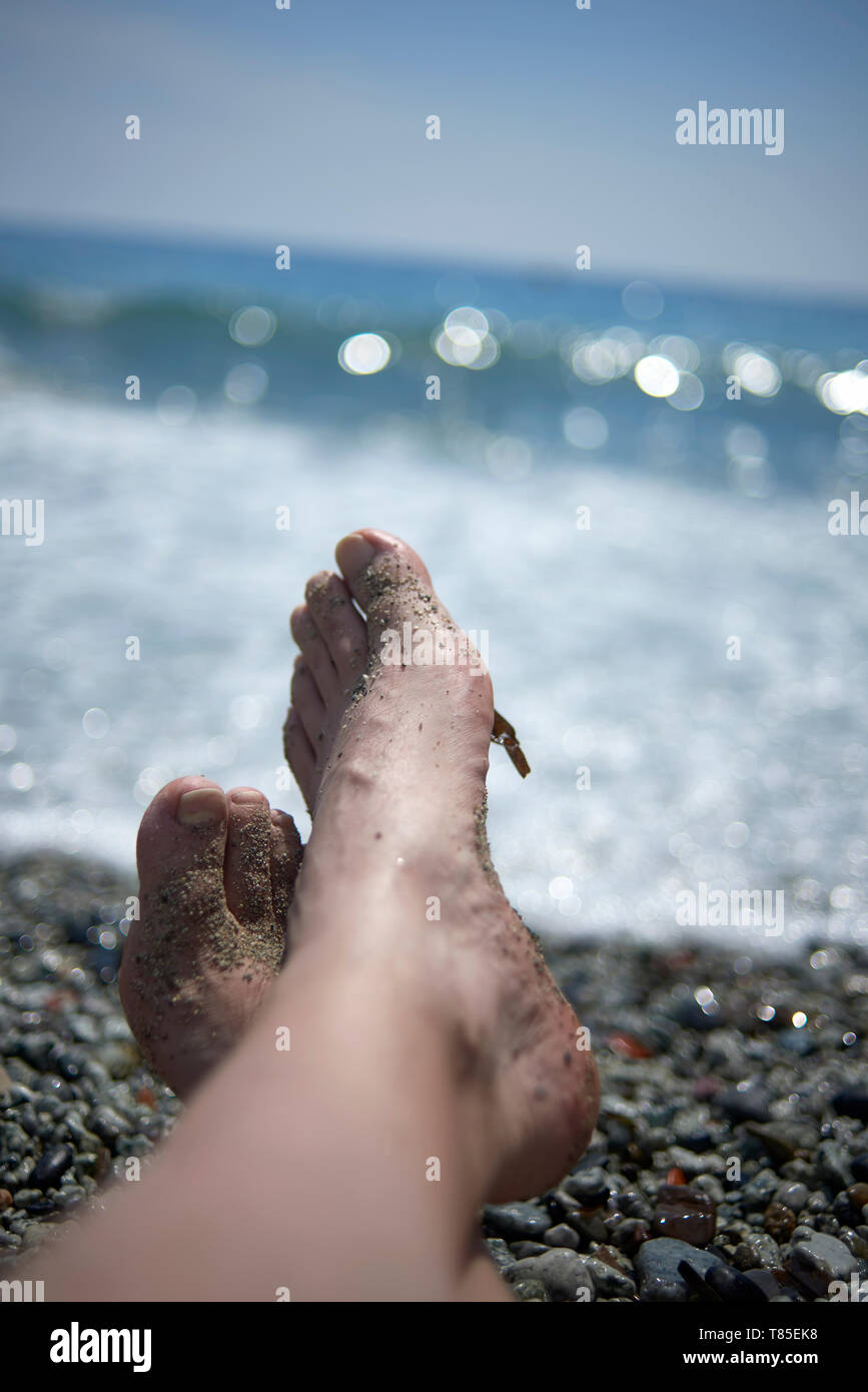 Close up of barefeet resting at the beach with the sea out of focus in the background - Stock Image