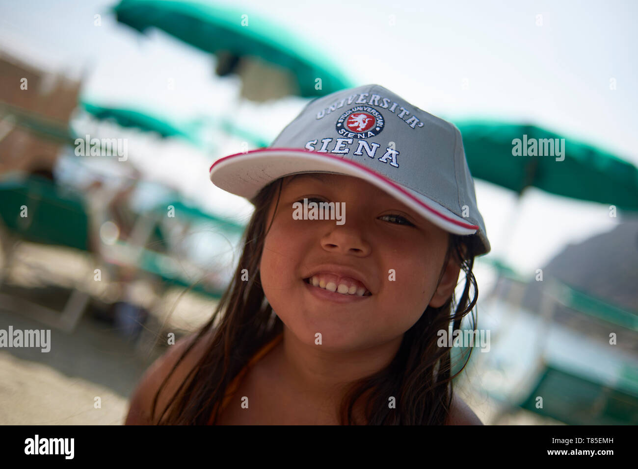 Cute Asian girl wearing a baseball cap from Siena smiling into camera whilst having fun at the beach in summer sunshine - Stock Image