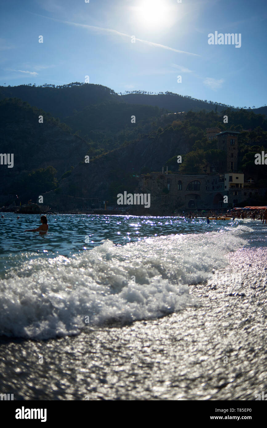 Beautiful landscape shot of the beach front and the waves crashing on shore in the Cinque Terra region of Italy in summer sunshine - Stock Image