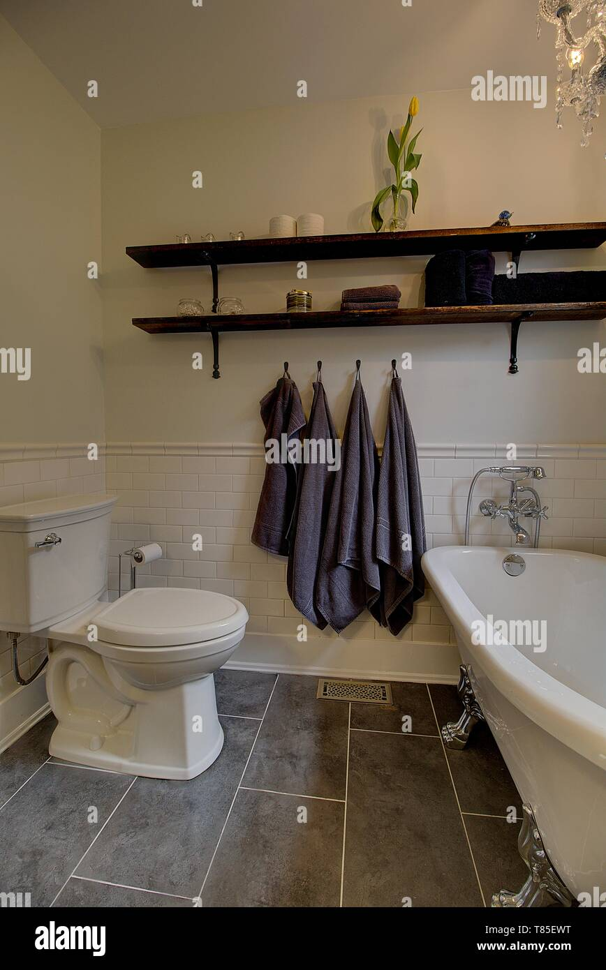 Updated bathroom with subway tile, claw foot tub, vintage wooden shelving. Contemporary home decor. - Stock Image