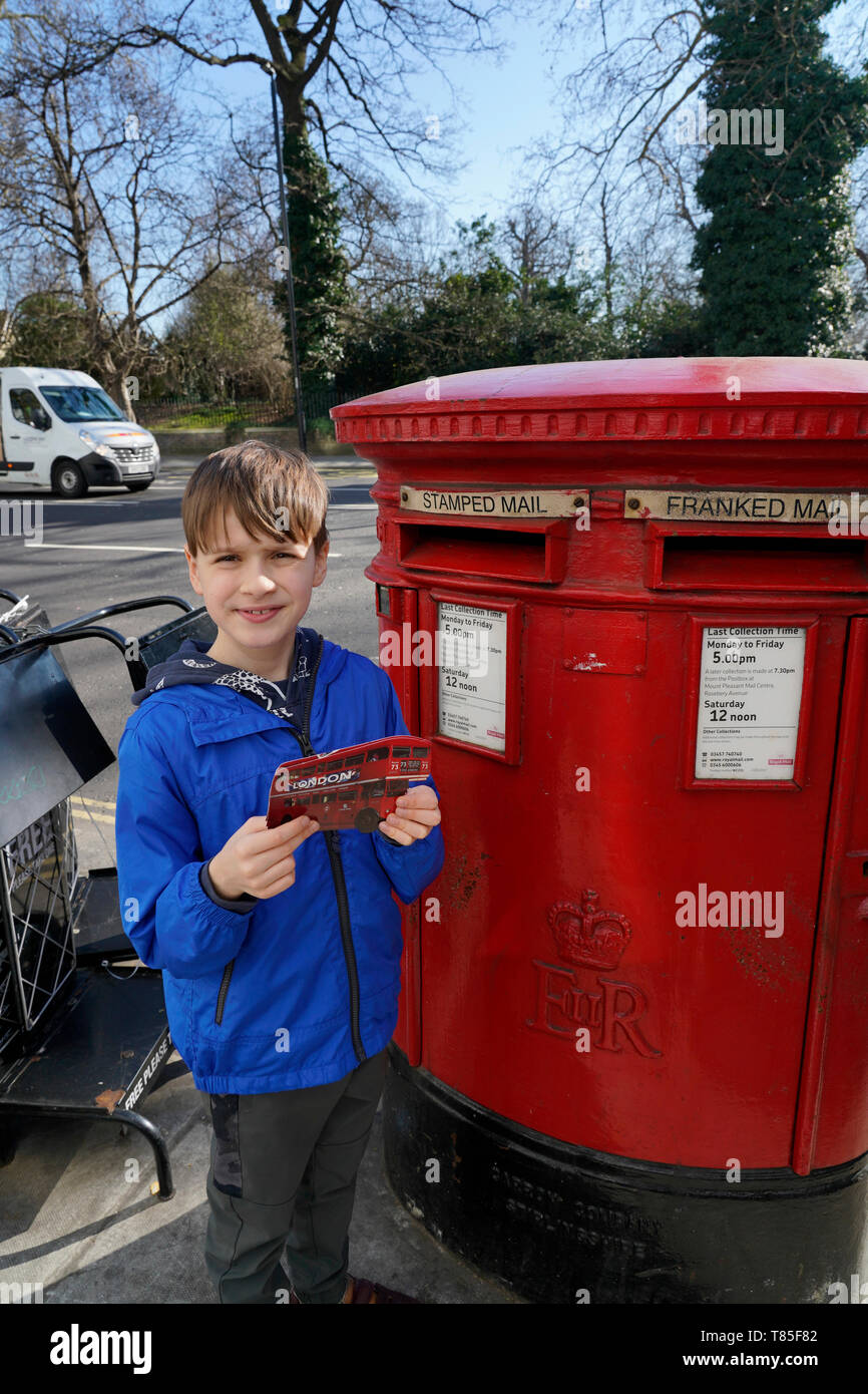 A boy posting a postcard in a red postbox in London, UK - Stock Image