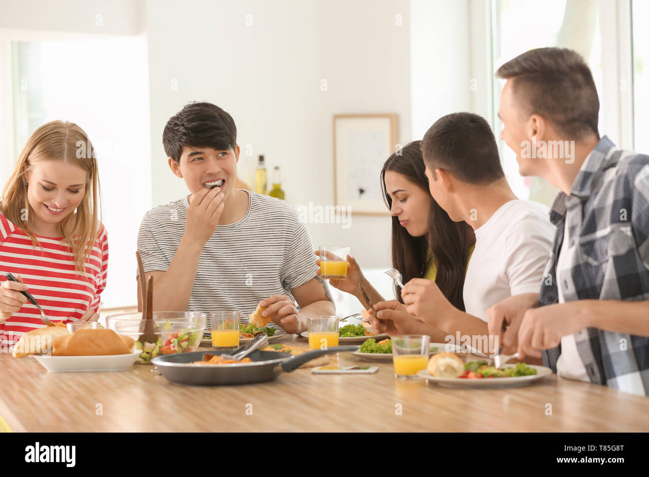 Astonishing Friends Eating At Table In Kitchen Stock Photo 245984952 Download Free Architecture Designs Embacsunscenecom