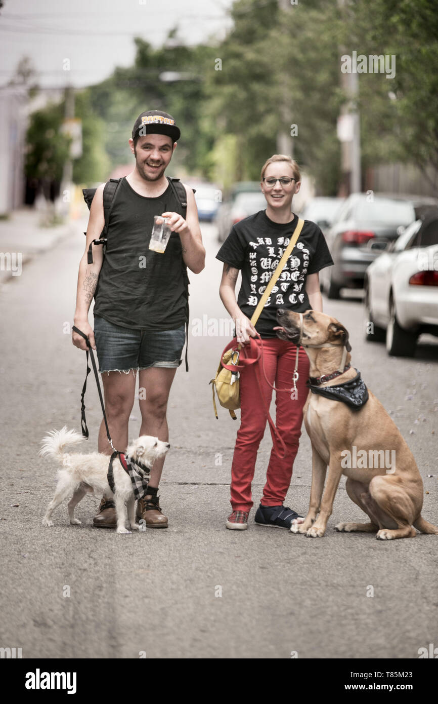 street portrait of a couple with 2 dogs on a walk in the Fishtown area of  Northern Philadelphia Pennsylvania, - Stock Image