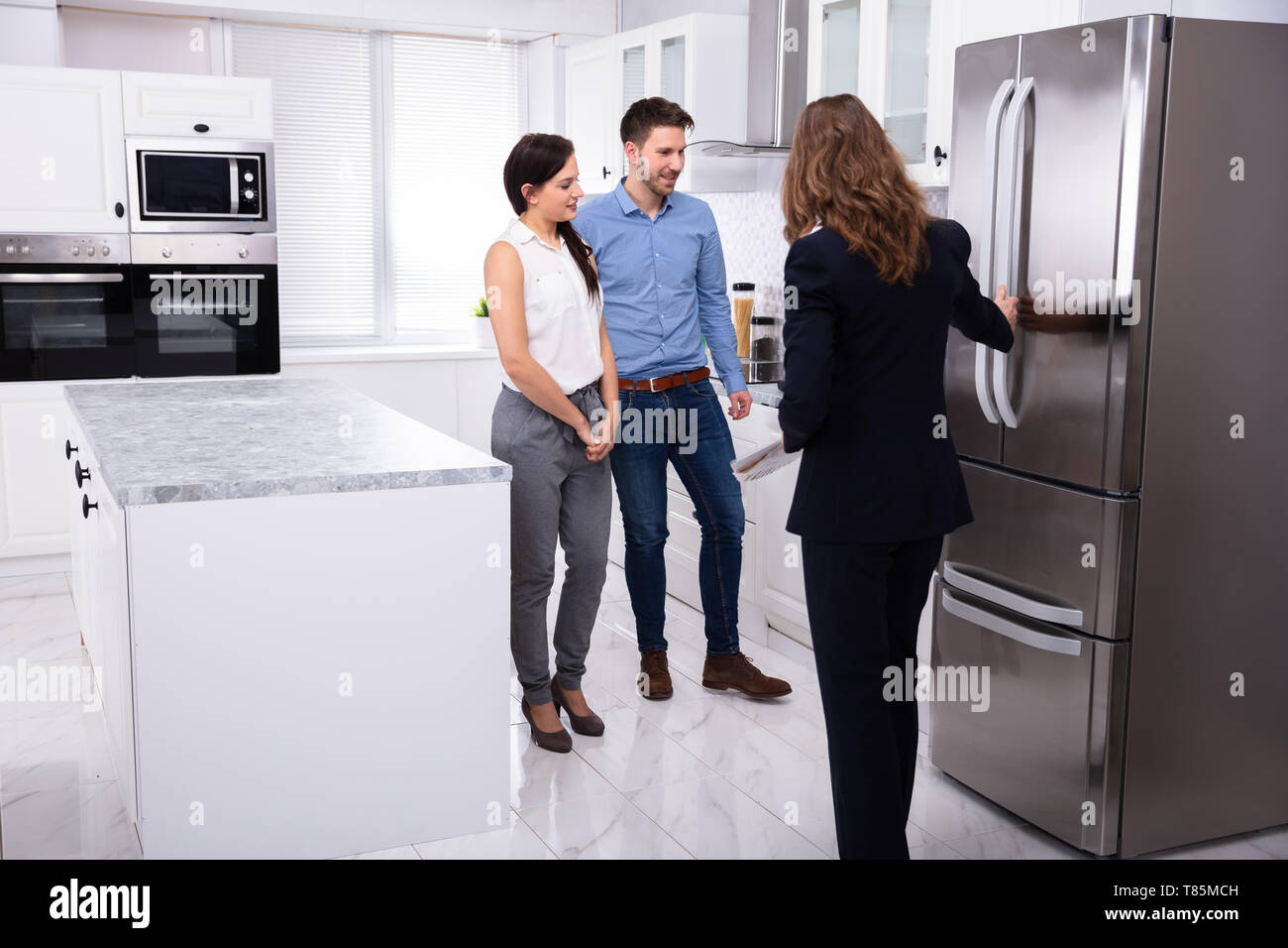Professional Real Estate Agent Showing Refrigerator In House To A Young Couple Stock Photo