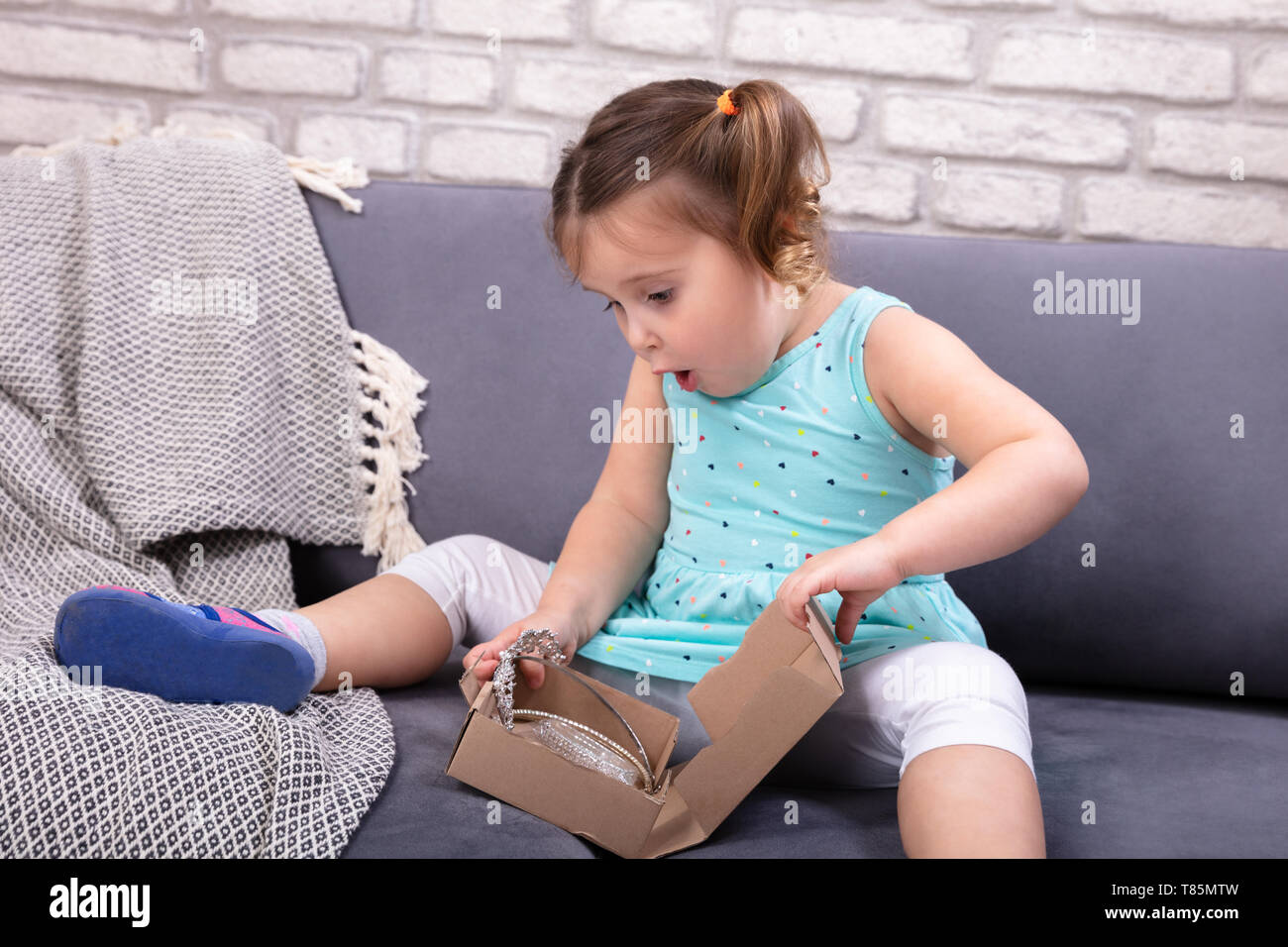 Surprise Little Girl Sitting On Sofa Opening Brown Parcel Box - Stock Image